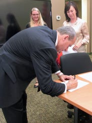 Robert Chabali signs paperwork after being sworn in