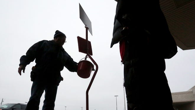 A man makes a donation at the Pick 'N Save grocery store in Weston while Salvation Army volunteer, Robert Konkel of Wausau, right, rings his bell, Tuesday, December 23, 2014.