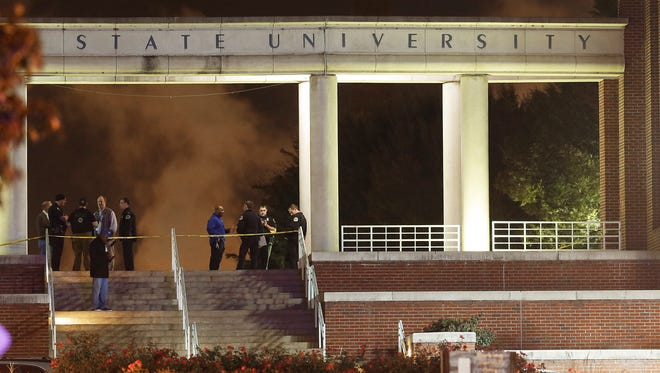 Officials investigate the scene of a shooting on the campus of Tennessee State University, early Friday, Oct. 23, 2015, in Nashville. Authorities say one person was killed and three injured in the Thursday shooting at an outdoor courtyard. The person who died did not attend the university, a school spokeswoman said.