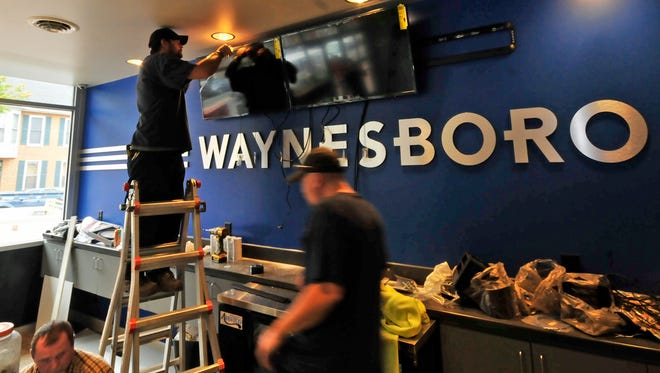 Workers install TV monitors Wednesday, Nov. 18, 2015 at the remodeled Waynesboro Theatre. The theater will reopen this weekend.