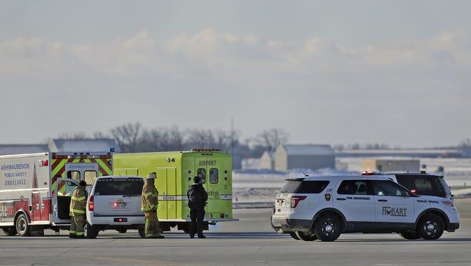 Emergency crews from Ashwaubenon, Hobart and Green Bay wait near the runway Friday during an emergency call at Green Bay Austin Straubel International Airport in Ashwaubenon.