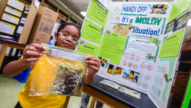 Khira Griffin, 7, holds up a slice of moldy bread that served as an integral part of her science project she presented during the 40th Annual Island Wide Science Fair at the University of Guam in Mangilao on Saturday, May 5, 2018. Griffin is a second-grader from Chief Brodie Memorial Elementary School.