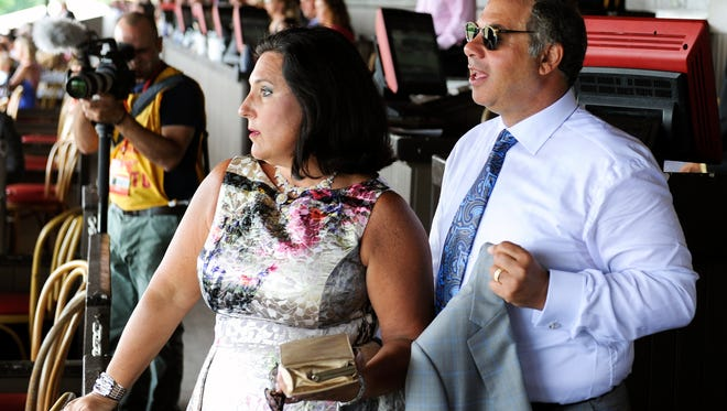 Joanne Zayat ,left, and her husband Ahmed Zayat, owners of Triple Crown winner American Pharoah arrive to watch Travers Day horse racing prior to the Travers Stakes at Saratoga Race Course in Saratoga Springs, N.Y., Saturday, Aug. 29, 2015. (AP Photo/Hans Pennink)