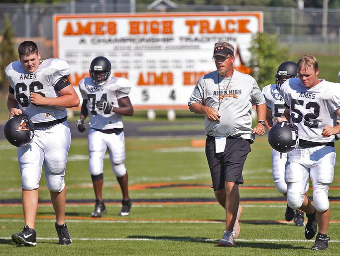 Ames head coach Bruce Vertanen leads his players to the other side of the field during drills at football practice at the high school in Ames on Tuesday, Aug. 19, 2014.