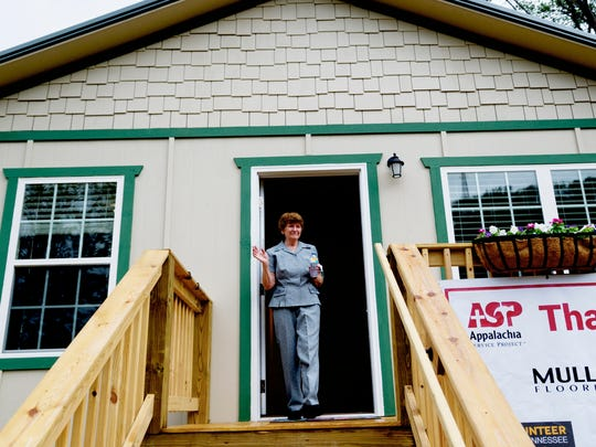 Glenna Ogle walks from her new home during the house dedication ceremony for Glenna Ogle, who lost her home during the November 28 wildfires in Gatlinburg, Tennessee on Friday, July 28, 2017. The home is the first of 25 homes to be built for fire victims by Appalachia Service Project.