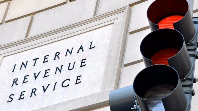 Internal Revenue Service plaque next to red traffic light.