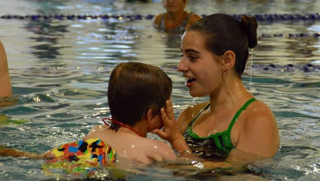 Katie Flegg, an instructor at the Hunterdon County Y, congratulates a student on his swimming success.