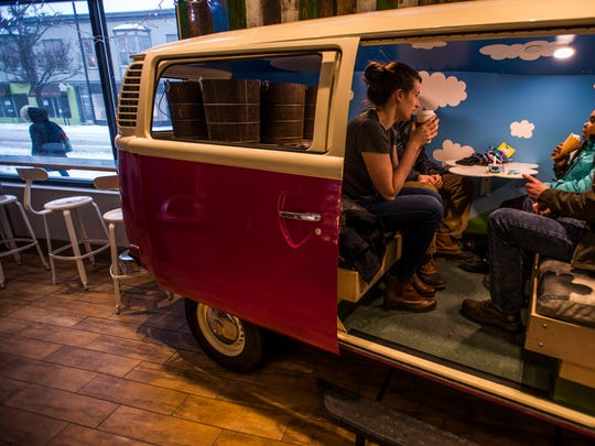 Armed with hot chocolate and even a few ice creams, folks cozy up in the VW bus inside Ben & Jerry's scoop shop on Church Street in Burlington, Vt., on Thursday afternoon, Jan. 4, 2018, as a bomb cyclone descended on the New England.