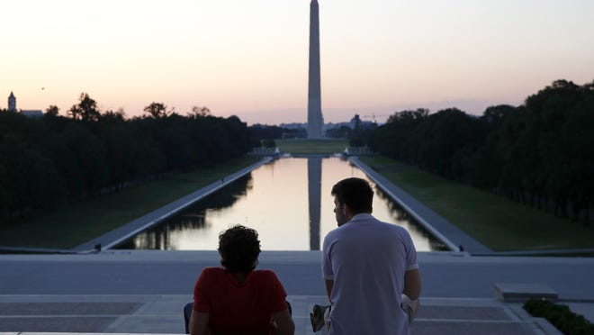 FILE - In this June 7, 2020, file photo, visitors watch sunrise from the Lincoln Memorial steps in Washington, the morning after massive protests over the death of George Floyd, who died after being restrained by Minneapolis police officers.