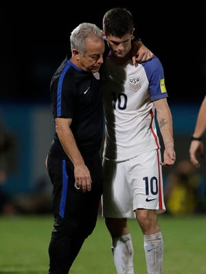 United States' Christian Pulisic is comforted by a member of the team staff after the U.S. lost to Trinidad and Tobago in their must-win World Cup qualifying match.