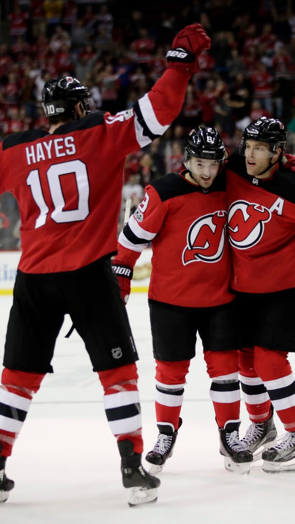 New Jersey Devils left wing Taylor Hall, right, celebrates his power-play goal with teammates Will Butcher, center, and Jimmy Hayes during the second period of an NHL hockey game against the Washington Capitals, Friday, Oct. 13, 2017, in Newark, N.J. (AP Photo/Julio Cortez)