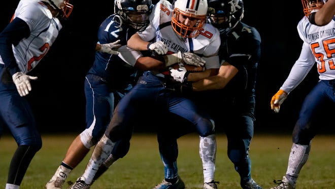 Richmond's Spencer Trapiss and Andrew Hamel bring down Flint Powers Catholic's Reese Morgan during a regional final football game Friday, November 13, 2015 at Richmond High School.