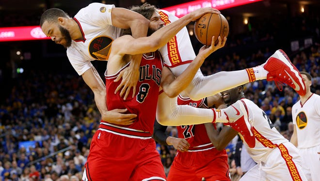 Chicago Bulls center Robin Lopez (8) is fouled by Golden State Warriors center JaVale McGee (1) while attempting a shot in the third quarter at Oracle Arena. The Warriors defeated the Bulls 123-92.