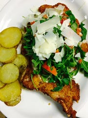 A lightly breaded thin-cut pork chop is topped with lemon butter sauce, arugula and tomatoes, served with roasted potatoes at Gusto Cucina Italiana in Cape Coral.