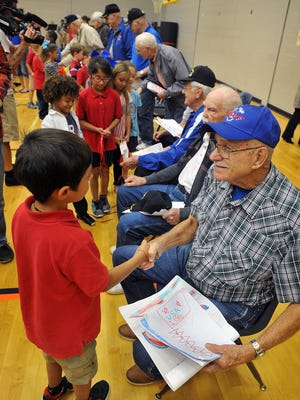 Wayne Sykes, a veteran of the Korean War, accepts pictures and greetings from students at Jefferson Elementary Thursday morning. Sykes and eight other veterans will leave Friday morning from DFW Airport on an Honor Flight to Washington DC.