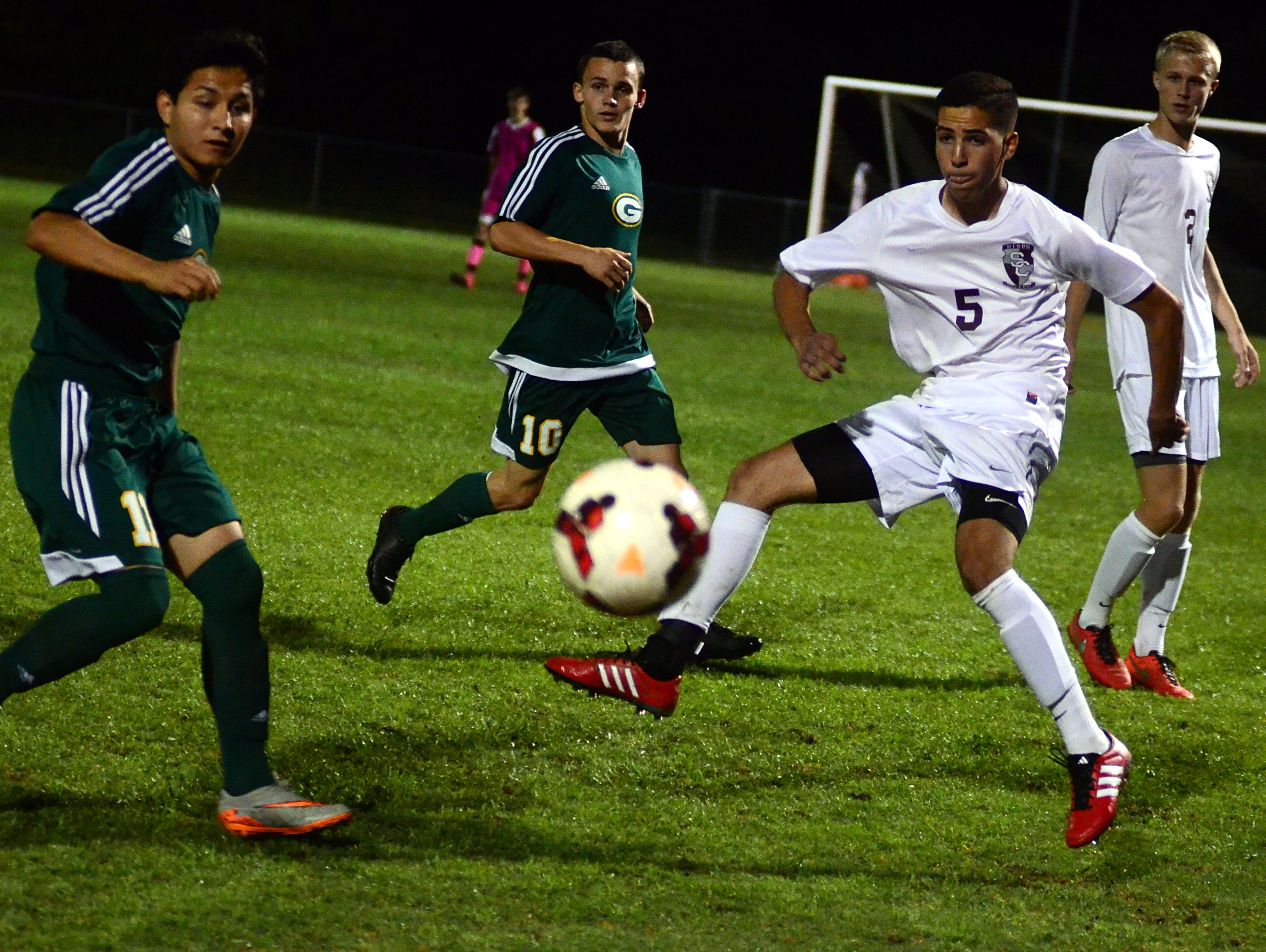 Station Camp High senior Dylan Grimsley clears the ball away from Gallatin junior Antonio Aquino (left) during first-half action.
