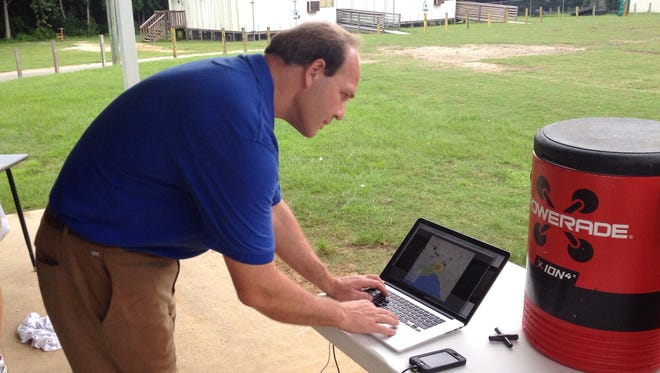 Meteorologist and WeatherSTEM founder Edward Mansouri checks the laptop displaying lightning strikes in the area during Lincoln's football practice Tuesday.