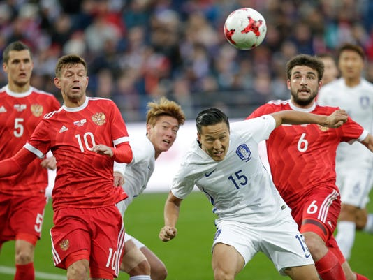 South Korea's Kyungwon Kwon, center right, challenges for the ball with Russia's Georgiy Dzhikiya, second from right, during the international friendly soccer match between Russia and South Korea in Moscow, Russia, Saturday, Oct. 7, 2017. (AP Photo/Pavel Golovkin)