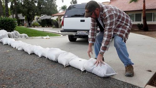Richard Pope places sand bags along his driveway to protect his home from an expected storm in Glendora, Calif. on Monday.  California is bracing for the arrival of a new, more powerful Pacific storm following a weekend of scattered rain, showers and snow. The National Weather Service says a low-pressure system off the coast will draw a plume of subtropical moisture northward into the state beginning today.