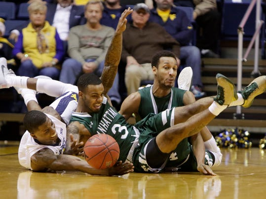 West Virginia guard Teyvon Myers (0), left, Manhattan guard Zavier Turner (3), center, and forward Calvin Crawford (14), right, dive for a loose ball during the first half of an NCAA college basketball game, Monday, Nov. 28, 2016, in Morgantown, W.Va. (AP Photo/Raymond Thompson)