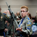 Firearms training unit Detective Barbara J. Mattson of the Connecticut State Police holds up a Bushmaster AR-15, the same make and model  gun used by Adam Lanza in the Sandy Hook School shooting, for a demonstration during a hearing at the Legislative Office Building in Hartford, Conn., in January 2013.