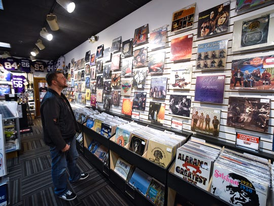 Music specialist Jeff Pederson talks about the variety of vinyl albums on display Thursday, Nov. 3, at Fan HQ Rock N Jock inside Crossroads Center in St. Cloud.