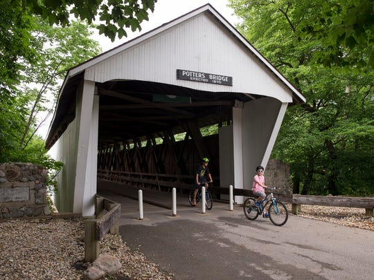Bike riders emerge from the span of Potters Bridge,