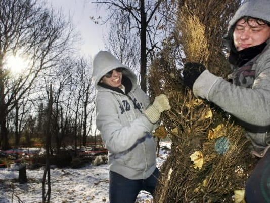 Matt Pyne, left, and Ben Myers, right, both juniors at  York  Catholic High School, help clear discarded trees and brush from a former dump site behind the school in January.