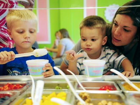 Jackson Schellenberger, 6, of Windsor Township, adds kiwi pieces to his frozen yogurt as Jackson Poff, 3, of Springettsbury Township, points out a topping he wants for his yogurt. His mother, Alicea, holds him up to the counter, last week.