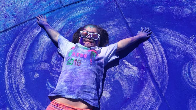 """Gaby Hernandez, 8, makes a """"color angel"""" during the Kolor Me 4 Kids Fun Walk/Run at Great Falls College Montana State University."""