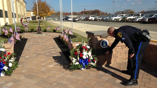 Gloucester Township Police Sgt. James Clark finds his name on a plaque at a Highland High School memorial dedicated to alumni military service.