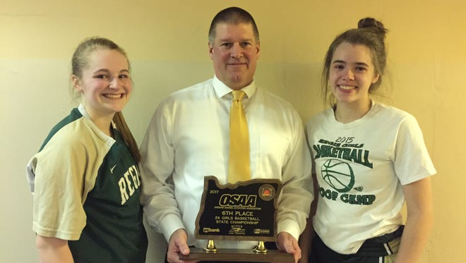 Regis coach Stuart Alley, center, holds the Class 2A sixth-place trophy with seniors Hadyn Moll, left, and Victoria Clute.