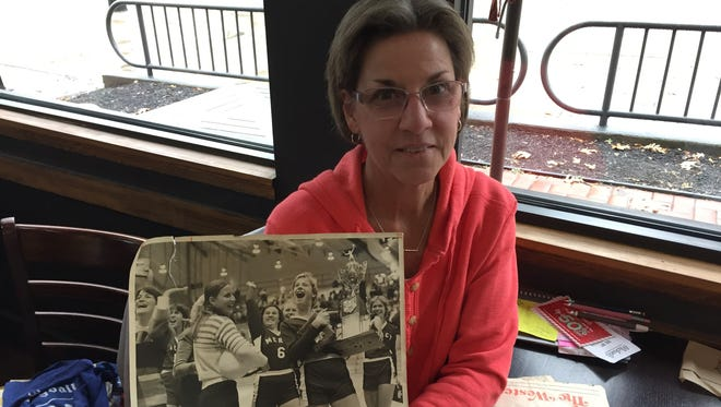 Rose Koch displays a photo of her and Mercy junior Nancy Holstegge (6) standing with senior team captain Terri Nichting, who is proudly displaying the Bobcats' 1977 volleyball state championship trophy.