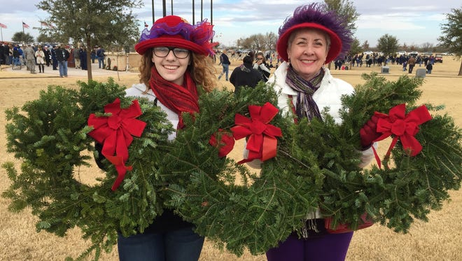Queen Mother Barbara Stuart and granddaughter Alexis D'Agostino help to place some of the 27 wreaths the Red Hat Angels contributed to the 2017 Wreaths Across America campaign at the Texas State Veterans Cemetery.
