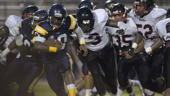 Carencro running back Tyriek Campbell (10) breaks away from a pack of Northside defenders before scoring a rushing touchdown during the first half of an LHSAA football game at Carencro High School in Carencro, La., Friday, Sept. 12, 2014.