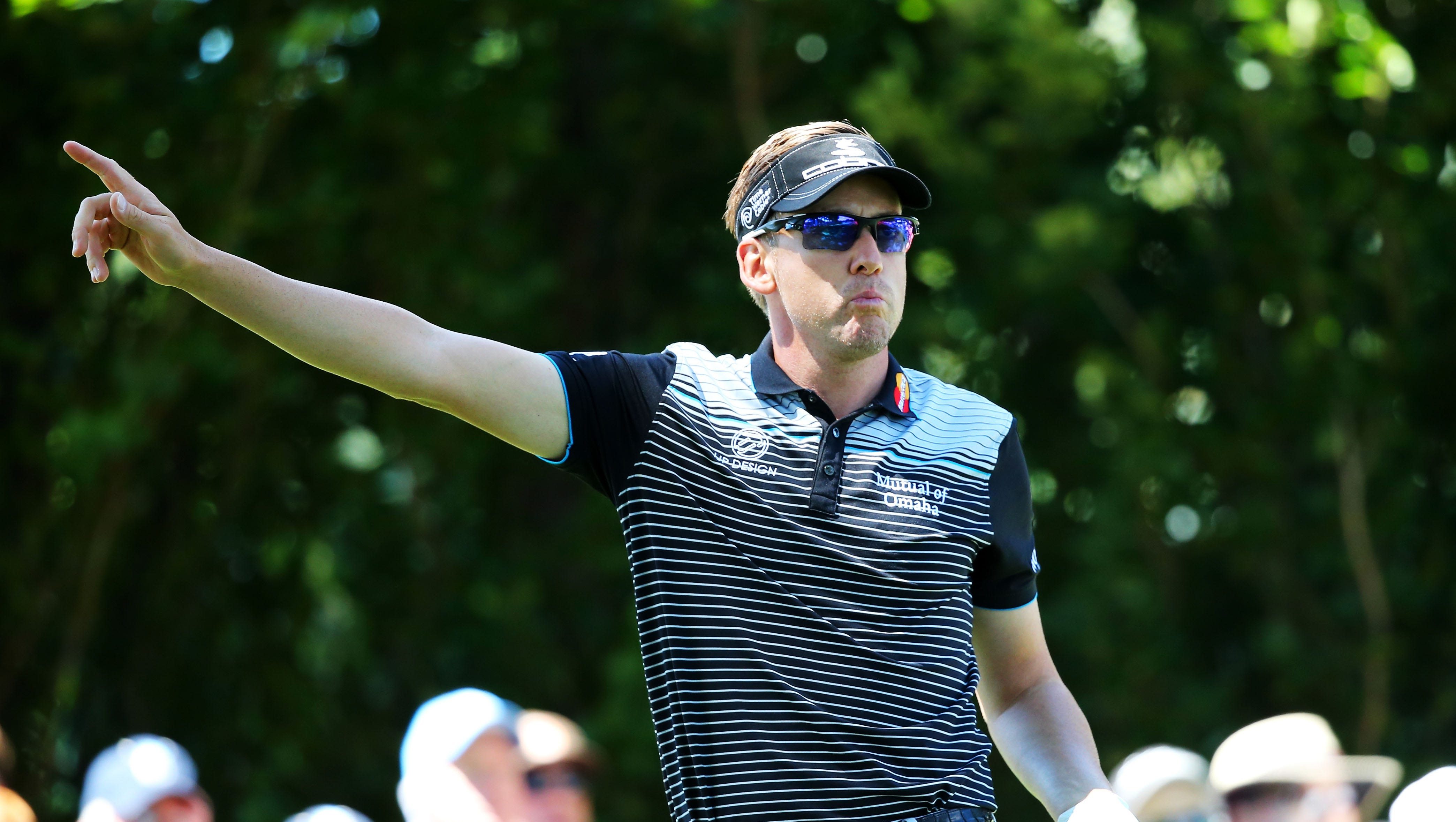 Ian Poulter of England signals after his tee shot on No. 10 flies wild.