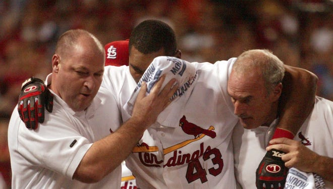 St. Louis Cardinals' outfielder Juan Encarnacion is helped off the field after being hit in the head by a foul ball from second baseman Aaron Miles on Aug. 31, 2007.