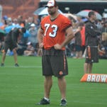 Browns left tackle Joe Thomas looks on in the rain as his fellow offensive linemen go through drills during Monday's practice.