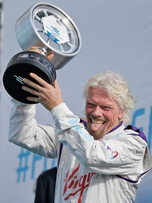 Virgin Racing Team owner Richard Branson prepares to present the second place trophy to Andretti Formula E team driver Scott Speed after the Formula E Miami ePrix auto race last Saturday in Miami