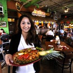Server Luis Medina carries generously portioned plates of sizzling food to patrons during the lunch hour.