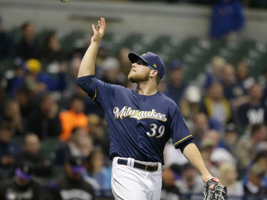 Milwaukee Brewers' Corbin Burnes grabs the ball after giving up a run to the Colorado Rockies during the sixth inning of a baseball game Wednesday, May 1, 2019, in Milwaukee. (AP Photo/Jeffrey Phelps)