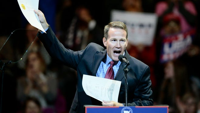 Ohio Secretary of State Jon Husted waves the papers he signed confirming Ohio in favor of Donald Trump during the first stop of Trump's post-election tour in Cincinnati on Dec. 1, 2016.