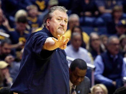 West Virginia head coach Bob Huggins signals a play to this team during the first half of an NCAA college basketball game against Oklahoma State, Saturday, Feb. 10, 2018, in Morgantown, W.Va. (AP Photo/Raymond Thompson)