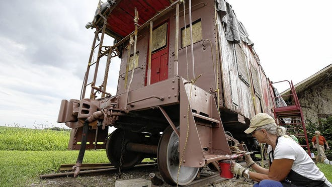 Rain Burroughs with the Southwest Franklin County Historical Society works on this 1929 C-2202 caboose Aug. 18 on a farm owned by William and Doris Green on Thrailkill Road in Orient.