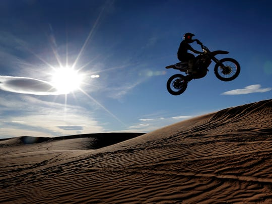 Travis Waters soars over the dunes Dec. 11 at Red Sands in far East El Paso. The county is considering closing the dunes to the public.