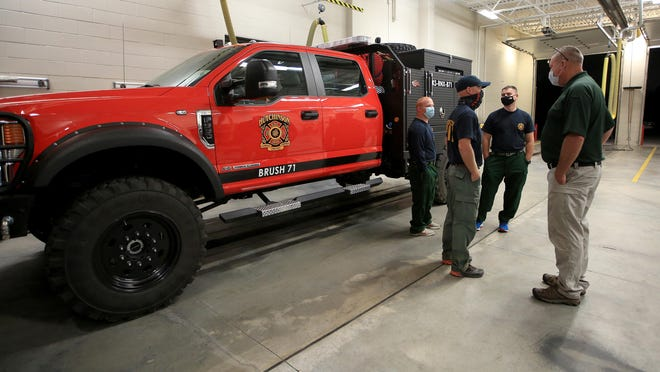 Hutchinson Fire Chief Steve Beer, right, talks to firefighters Jacob Ice, left, Brent Fisher and Caleb Dunn, back, just before they deployed Wednesday morning from Station 7 on E. 30th Avenue for their trip to Wyoming to fight wildfires.