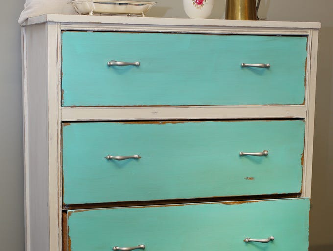 A high boy dresser painted in vibrant turquoise is accented with brushed silver pulls. ($100 at Southport Antique Mall).