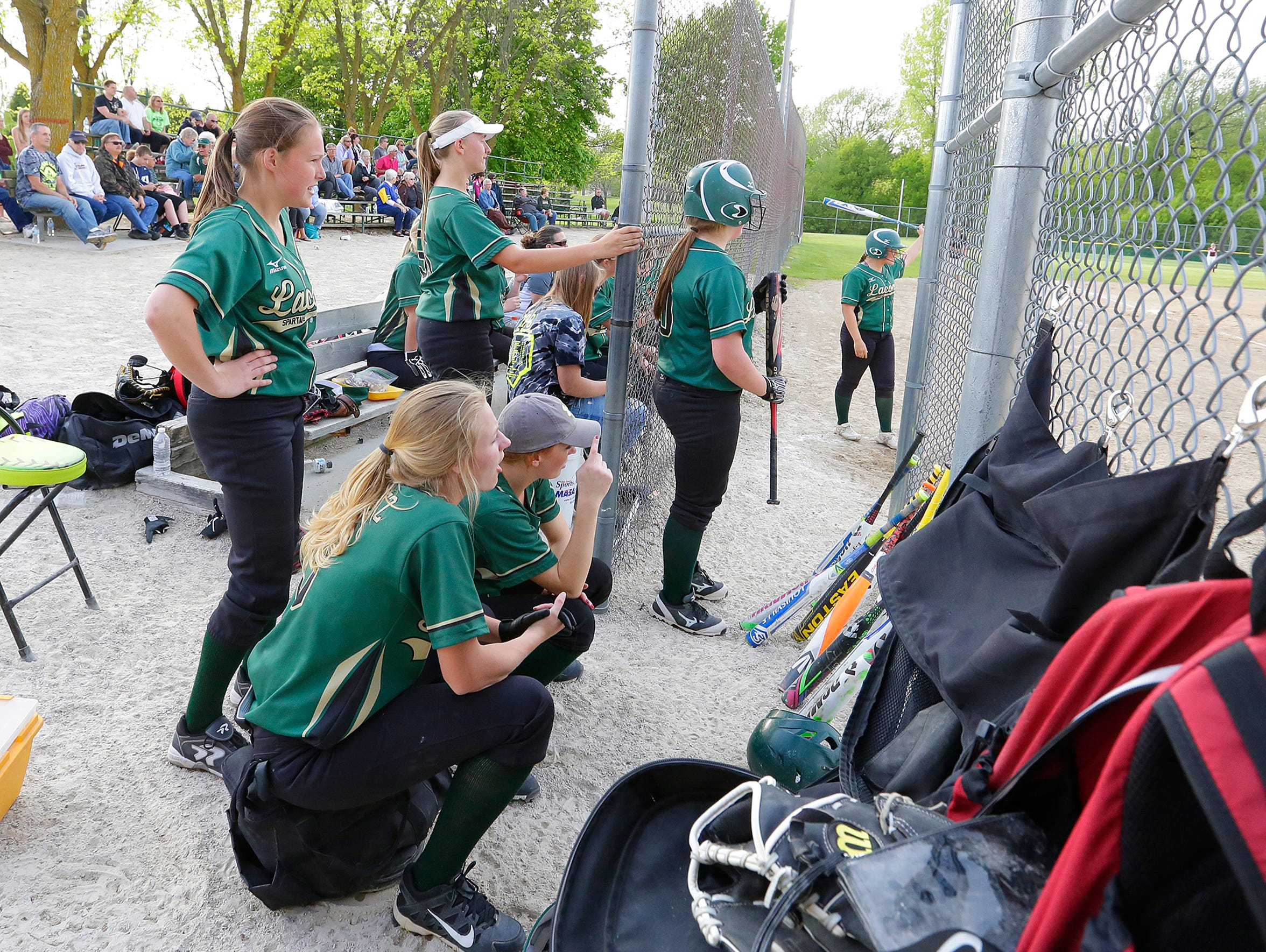 The Laconia softball team cheers from the bench during