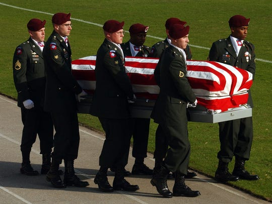 An honor guard carries the casket of Army Chief Warrant