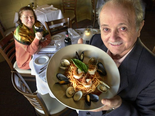 The Pizzi family has been running Italian restaurants in Indianapolis since 1979. They open a new one in fall 2018 at the Fountain Square Theatre building.  Pictured here is family patriarch Joe Pizzi, showing off pasta with seafood, and his wife, Anna Pizzi.